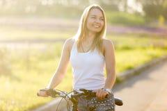 Mujer joven de risa en la bicicleta en luz del sol Foto de archivo libre de regalías
