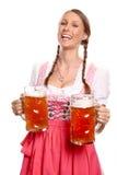 Mujer joven de risa en una cerveza de la porción del dirndl Foto de archivo