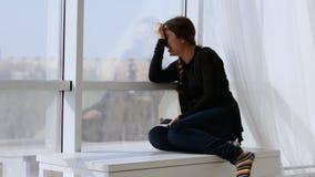 Mujer joven de risa feliz que mira en la cámara El sentarse en la ventana en los rayos del sol de la primavera metrajes