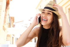 Mujer joven de risa que escucha el teléfono móvil Imagen de archivo libre de regalías