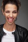 Mujer joven de risa que guiña con la lengua hacia fuera Imagenes de archivo
