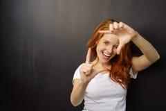 Mujer joven de risa que hace un gesto del marco Foto de archivo
