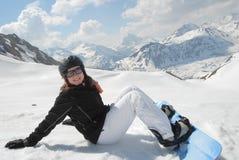 Mujer joven de risa que se sienta en nieve con snowboar Fotos de archivo