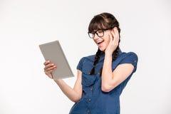 Mujer joven de risa que usa la tableta Imágenes de archivo libres de regalías