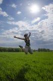 Mujer joven de salto en el campo Foto de archivo