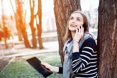 Mujer joven de Smilling con la tableta digital a disposición que habla en el teléfono móvil con el novio antes de una reunión con Imágenes de archivo libres de regalías