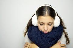 Mujer joven de temblor que mira abajo de enfermedad con gripe o frío Mujer joven que es orejeras, scraf y suéter que llevan fríos Imagen de archivo