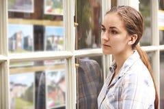 Mujer joven decepcionada que mira en la ventana de agentes de la propiedad inmobiliaria fotos de archivo