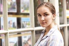 Mujer joven decepcionada que mira en la ventana de agentes de la propiedad inmobiliaria foto de archivo