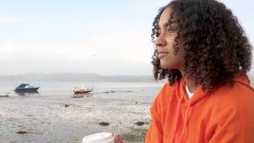 Mujer joven del adolescente afroamericano Biracial de la muchacha que lleva la sudadera con capucha anaranjada, café para llevar  almacen de metraje de vídeo