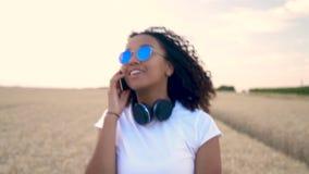 Mujer joven del adolescente afroamericano de la muchacha en la camiseta blanca y gafas de sol azules que camina hablar en su telé almacen de metraje de vídeo