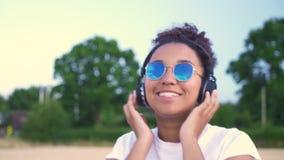 Mujer joven del adolescente afroamericano de la muchacha en la camiseta blanca y gafas de sol azules que escucha la música en los almacen de metraje de vídeo