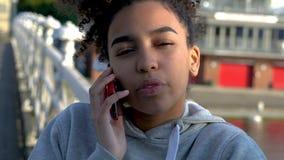 Mujer joven del adolescente de la muchacha en un puente sobre un río, hablando en un teléfono celular móvil almacen de video