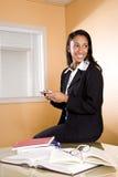 Mujer joven del African-American texting y que estudia Fotos de archivo