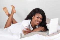 Mujer joven del Afro puesta delante de una computadora portátil Foto de archivo libre de regalías
