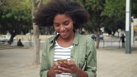 Mujer joven del Afro que camina y que usa el móvil en la ciudad almacen de metraje de vídeo