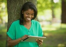 Mujer joven del afroamericano en el ordenador de la tablilla Imagen de archivo libre de regalías