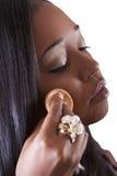 Mujer joven del afroamericano que aplica la cara del maquillaje Fotos de archivo