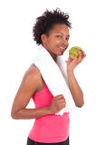 Mujer joven del afroamericano que come una manzana Fotos de archivo