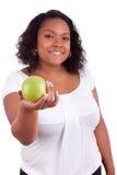 Mujer joven del afroamericano que da una manzana verde Imagenes de archivo