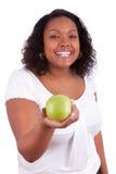 Mujer joven del afroamericano que da una manzana verde Foto de archivo