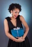 Mujer joven del afroamericano que sostiene un regalo Fotografía de archivo libre de regalías
