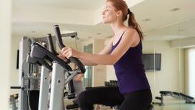 Mujer joven del ajuste juguetón en el gimnasio que hace ejercicios en la bicicleta estática Pesos de elevación del individuo en f metrajes