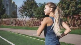 Mujer joven del ajuste sano que corre en una pista de los deportes en un estadio almacen de metraje de vídeo