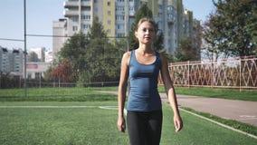Mujer joven del ajuste sano que corre en una pista de los deportes en un estadio almacen de video