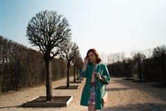 Mujer joven del amante de la moda waling en un parque que lleva la chaqueta verde viva y una falda colorida imagenes de archivo