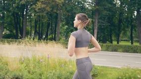 Mujer joven del atleta que corre en parque del verano en el entrenamiento de la mañana almacen de video