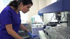 Mujer joven del ayudante de laboratorio del retrato en uniforme azul y los guantes de goma que controlan la fabricación de la dro metrajes