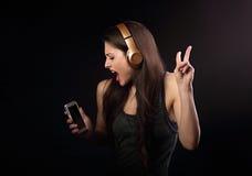 Mujer joven del baile hermoso que escucha la música, mostrando sig de v Imagenes de archivo