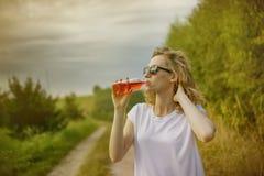 Mujer joven del beautifil que bebe la bebida no alcohólica roja Foto de archivo