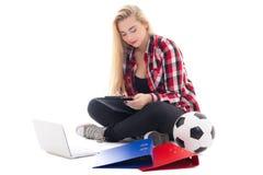 Mujer joven del blondie que se sienta con el ordenador portátil, las carpetas y el balón de fútbol Imagen de archivo