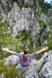 Mujer joven del caminante que estira sus brazos en la montaña Imagen de archivo libre de regalías