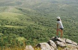 Mujer joven del caminante que se coloca en el pico de la roca Foto de archivo