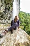 Mujer joven del caminante que se sienta en una roca Imagenes de archivo