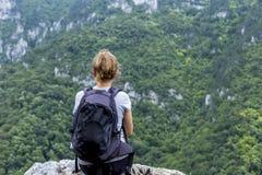 Mujer joven del caminante que se sienta en una roca con la mochila Foto de archivo libre de regalías