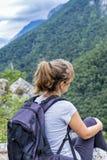 Mujer joven del caminante que se sienta en una roca con la mochila Fotos de archivo
