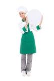 Mujer joven del cocinero en el uniforme que sostiene la placa vacía grande con el copysp fotografía de archivo libre de regalías