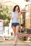 Mujer joven del cuerpo completo que habla en el teléfono celular afuera en verano foto de archivo