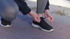 Mujer joven del deporte que ata las zapatillas deportivas durante almacen de video