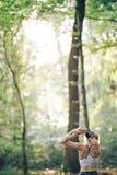 Mujer joven del deporte que hace ejercicios durante el entrenamiento afuera en parque de la ciudad Foto de archivo