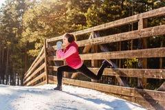 Mujer joven del deporte que hace ejercicios durante el entrenamiento del invierno afuera Imagen de archivo