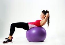 Mujer joven del deporte que hace entrenamiento del ABS en fitball Imagenes de archivo