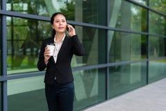 Mujer joven del encargado que se coloca en el edificio moderno Imagen de archivo libre de regalías