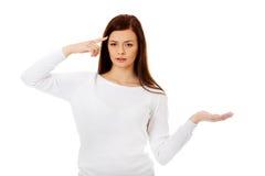 Mujer joven del estudiante que lleva a cabo algo en la palma abierta Fotografía de archivo libre de regalías