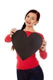Mujer joven del estudiante que lleva a cabo el corazón de papel negro Fotos de archivo
