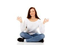 Mujer joven del estudiante que sienta y que hace yoga Imagen de archivo libre de regalías